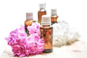 Four empty bottles for essential oils next to pink flowers